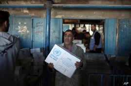 Palestinians receive food aid at a U.N. Relief and Works Agency warehouse in the Shati refugee camp, Gaza City, Jan. 14, 2018.