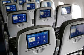 This March 16, 2017, photo shows the interior of a JetBlue airliner at John F. Kennedy International Airport in New York. Government figures show that U.S. airlines are improving at flying on time, handling baggage and not bumping as many passengers.
