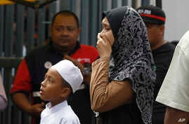 Unidentified Malaysians cry outside an Islamic religious school following a fire on the outskirts of Kuala Lumpur, Sept. 14, 2017. The official said the fire, which killed mostly teenagers, started early Thursday at the top floor of the three-story b