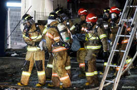 A victim is carried by firefighters in Jecheon, South Korea, Dece. 21, 2017.