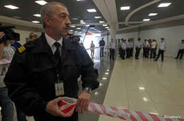 Russian airport security staff secure an area after former U.S. spy agency contractor Edward Snowden was granted documents that will allow him to leave the transit area of Sheremetyevo airport in Moscow, July 24, 2013.