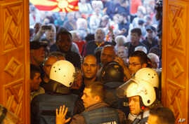 Police try to block protestors as they enter into the parliament building in Skopje, Macedonia, April 27, 2017. Scores of protesters have broken through a police cordon and entered Macedonian parliament to protest the election of a new speaker despit