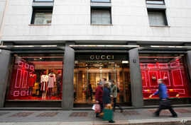 FILE - People walk in front of Gucci shop in Monte Napoleone street in Milan, Italy, Oct. 20, 2016. Nigerian women who were trafficked to Italy to work as prostitutes have found new work in a handbag and dressmaking shop that recently received fabric