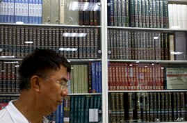 A Chinese man walks by a cabinets displaying Chinese encyclopedias at a book store in Beijing, May 4, 2017.