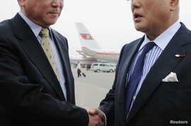Japanese Cabinet Secretariat Advisor Isao Iijima (R) is greeted by Kim Chol-ho, vice director of the North Korean Foreign Ministry's Asian Affairs Department, upon his arrival Pyongyang airport, May 14. 2013.