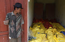 A villager stands near body bags containing the dead bodies of asylum seekers, who were killed when their boat sank, at an Agrabinta health clinic on the outskirts of Sukabumi, Indonesia's West Java province, Sept. 28, 2013.