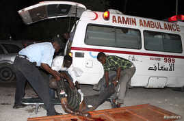 Somali policemen move a victim from a suicide strike at Village restaurant in Mogadishu September 20, 2012.