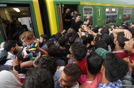 Migrants storm into a train at the Keleti train station in Budapest, Hungary, Sept. 3, 2015 as Hungarian police withdrew from the gates after two days of blocking their entry.
