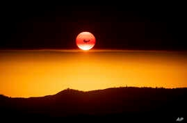 FILE - A plane battling the Ferguson Fire passes the setting sun over unincorporated Mariposa County, Calif., near Yosemite National Park, July 15, 2018.