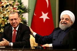 FILE - Iran's President Hassan Rouhani, right, laughs during a during a joint press conference with Turkey's President Recep Tayyip Erdogan following their meeting at the Saadabad Palace in Tehran, Iran, Oct. 4, 2017.