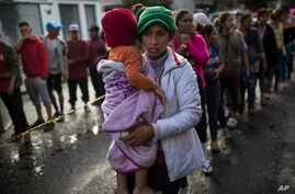 Maria del Carmen Mejia holds her daughter Britany Sofia while standing a line outside a migrant shelter in Tijuana, Mexico, Thursday, Nov. 22, 2018. U.S President Donald Trump threatened Thursday to close the U.S. border with Mexico for an undisclose