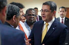 FILE - Honduran President Juan Orlando Hernandez, right, greets Honduran community leaders and guests, June 14, 2017, in Doral, Fla. Honduran community leaders and families raised their concerns with Hernandez about what will happen to them after the