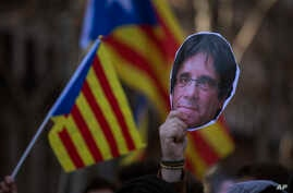 A demonstrator holds a mask of Catalonia's ex-president Carles Puigdemont during a protest outside the Catalonia parliament in Barcelona, Spain, Jan. 30, 2018.