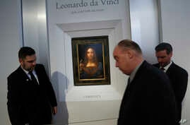 """Security guards set up a rope in front of """"Salvator Mundi"""" by Leonardo da Vinci during a news conference at Christie's in New York, Oct. 10, 2017."""