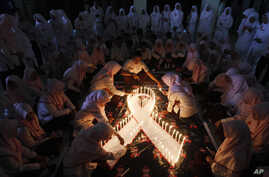 Indonesian medical students light candles during a vigil commemorating World AIDS day in Surabaya, East Java, Indonesia, Dec. 1, 2015.