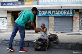 Mariano Marquez (L), a volunteer of Make The Difference (Haz La Diferencia) charity initiative, gives a cup of soup and an arepa to a homeless woman in a street of Caracas, Venezuela, March12, 2017.