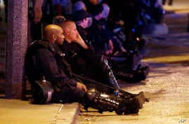 Police rest after multiple arrests were made following a protest in response to a not-guilty verdict in the trial of former St. Louis Police Officer Jason Stockley, Sept. 18, 2017, in St. Louis. Stockley was acquitted in the 2011 killing of a black m