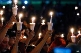 Attendees raise their candles at a candlelight vigil for the victims of the shooting at Marjory Stoneman Douglas High School, in Parkland, Fla., Feb. 15, 2018.