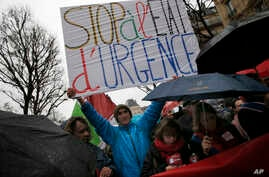 """A protester holds a banner reading """" Stop of state of emergency"""" during a protest in Paris, Jan. 30, 2016."""