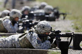 FILE - Female soldiers from 1st Brigade Combat Team, 101st Airborne Division train on a firing range while testing new body armor in Fort Campbell, Kentucky, Sept. 18, 2012.