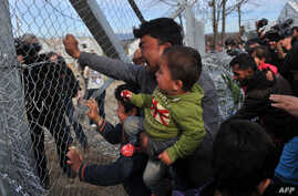 A man from Afghanistan carrying a baby cries as he pushes against the fence at the Greece-Macedonia border during a demonstration near the village of Idomeni, northern Greece, on February 22, 2016, against Macedonia's refusal to allow Afghans to pass