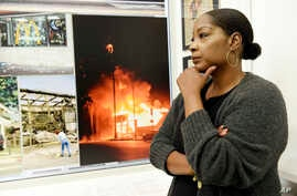 "Katynja McCory, lead docent for the ""Re-Imagine Justice"" art exhibit, looks at L.A. Riots photos featured in the exhibit at the Community Coalition, April 18, 2017. When she thinks back to the Rodney King riots, McCory recalls that her mother told th"