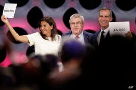 International Olympic Committee (IOC) President Thomas Bach stands between Paris Mayor Anne Hidalgo, left, and Los Angeles Mayor Eric Garrett at the end of the IOC session in Lima, Peru, Sept. 13, 2017.