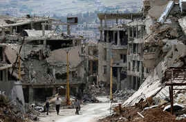 Residents walk through rubble with damaged electricity lines at the mountain resort town of Zabadani in the Damascus countryside, Syria, May 18, 2017.