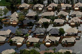 Homes are surrounded by water from the flooded Brazos River in the aftermath of Hurricane Harvey, in Freeport, Texas, Sept. 1, 2017.