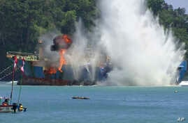 FILE - In this image made from video, an illegal fishing vessel that was seized by Indonesia's Navy is sunk in the waters off Pangandaran, West Java, Indonesia, March 14, 2016.
