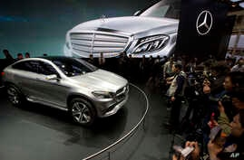 FILE - In this April 20, 2014 file photo, visitors look at the latest model from Mercedes at an auto show in Beijing. Nearly half of foreign companies in China feel singled out in a wave of anti-monopoly and other investigations, and a growing number