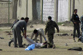 Afghan policemen and security personnel pick up a dead body after a suicide attack at an army recruitment center in Kunduz, March 14, 2011.