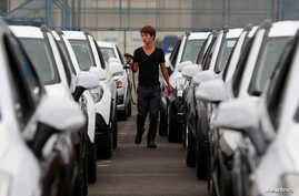 FILE - A worker checks cars made by GM Korea in a yard of GM Korea's Bupyeong plant before they are transported to a port for export, in Incheon, west of Seoul, Aug. 9, 2013.