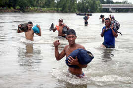 Central American migrants, part of a caravan trying to reach the U.S., cross the Suchiate River to avoid the border checkpoint in Ciudad Hidalgo, Mexico, Oct. 20, 2018.