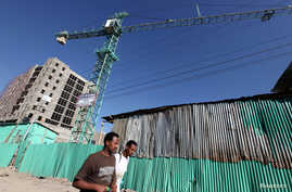 People walk past office blocks under construction in Ethiopia's capital Addis Ababa, January 27, 2010. There is a growing belief that the continent -- home to 53 countries, a rapidly urbanizing young population of a billion people and as much as a th