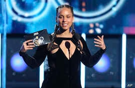 FILE - Alicia Keys presents the award for record of the year at the 60th annual Grammy Awards at Madison Square Garden in New York, Jan. 28, 2018.