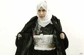 FILE - Iraqi Sajida Mubarek Atrous al-Rishawi opens her jacket and shows an explosive belt as she confesses to her failed bid to set off an explosives belt, in Amman, Jordan, Nov. 13, 2005.