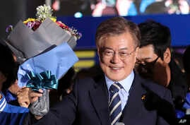 South Korea's presidential candidate Moon Jae-in of the Democratic Party smiles as he holds a bouquet of flowers during an election campaign in Seoul, South Korea, May 8, 2017.