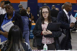 People speak with recruiters at a job fair in Uniondale, New York, Oct. 7, 2014.