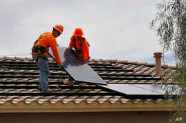 Electricians install solar panels on a roof for Arizona Public Service company in Goodyear, Arizona, June 1, 2016.
