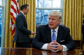 President Donald Trump sits at his desk as he waits for White House Chief of Staff Reince Priebus, left, to deliver three executive orders for his signature, Jan. 23, 2017, in the Oval Office of the White House in Washington.
