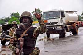 A Liberian soldier stops people at a security checkpoint set up to clamp down on people trying to travel to the capital from rural areas hard-hit by the Ebola virus, on the outskirts of Monrovia, Aug. 7, 2014.
