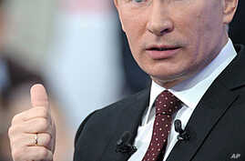 Russian Prime Minister Vladimir Putin gestures while a national call-in TV show in Moscow, Russia. Putin said Thursday the results of Russia's parliamentary election reflected the people's will, and that the opposition had alleged vote fraud purely t