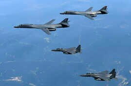 FILE - In this June 20, 2017, file photo provided by South Korean Defense Ministry, U.S. Air Force B-1B bombers, top, and second from top, and South Korean fighter jets F-15K fly over the Korean Peninsula, South Korea. A South Korean lawmaker said Oc