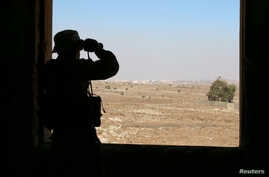 A rebel fighter looks through binoculars in Quneitra countryside, Syria, Sept. 10, 2016.