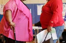 FILE - Two women converse in New York. New government figures released Friday, Oct. 13, 2017 showed small increases that were not considered statistically significant but were seen by some as a cause for concern. The adult obesity rate rose from to a