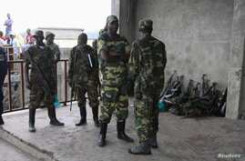 M23 rebels guard weapons given to them by the government's army in Goma November 21, 2012.