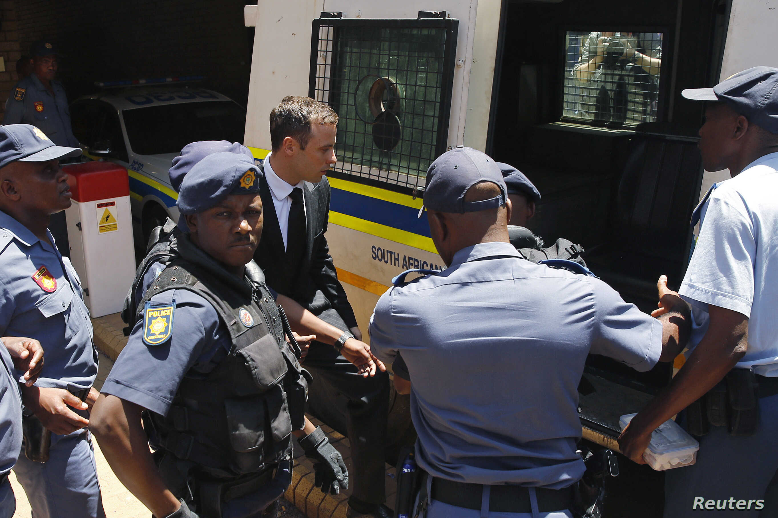 South African Olympic and Paralympic sprinter Oscar Pistorius, center, enters a police van after his sentencing at the North Gauteng High Court in Pretoria, Oct. 21, 2014.