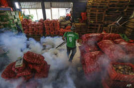 In this Jan. 28, 2016, photo, a Health Ministry worker fumigates for mosquitoes that transmit the Zika virus at the Oriental Market in Managua, Nicaragua.