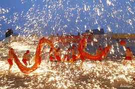 Dancers perform a fire dragon dance in the shower of molten iron spewing firework-like sparks during a folk art performance to celebrate the Chinese Lunar New Year at an amusement park in Beijing February 10, 2013.